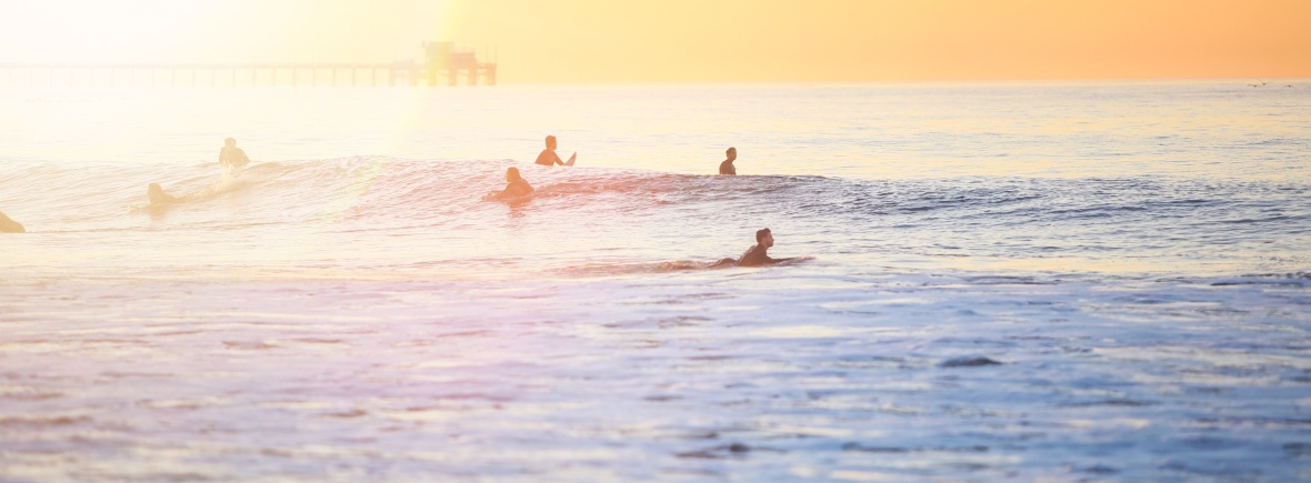 surfers in sea at dawn